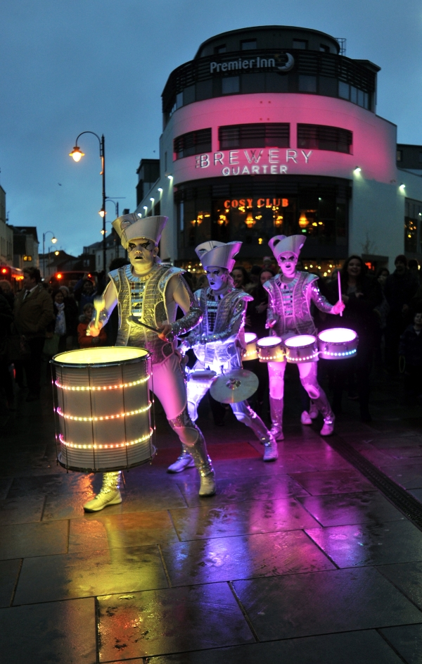 Spark! street drumming performers illumiated in multicolour lights outside The Brewery Quarter