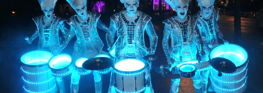 Spark! street drumming performers illuminated in blue light